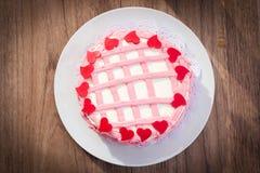 La torta con crema de la mantequilla adorna y chocolate rojo Imagen de archivo libre de regalías