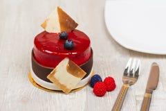 La torta con las bayas y la placa en la tabla Imagen de archivo libre de regalías