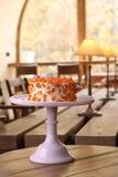 La torta cubierta en el blanco rodó la pasta de azúcar y adornado con las flores del mazapán en un soporte Fotos de archivo libres de regalías