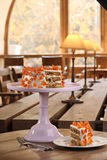 La torta cubierta en el blanco rodó la pasta de azúcar y adornado con las flores del mazapán en un soporte Fotos de archivo