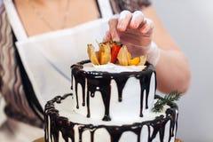 La torta de chocolate blanca poner crema con el esmalte del chocolate se adorna con las frutas Fotos de archivo