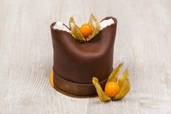 La torta de chocolate con dos bayas en la tabla Foto de archivo