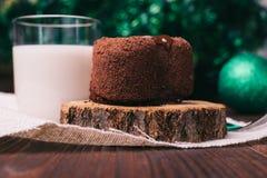 La torta de chocolate, un vidrio de leche y las decoraciones de la Navidad encendido cortejan Foto de archivo libre de regalías