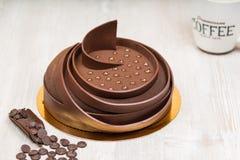 La torta de la torta con helar puntos y el café en la tabla Fotografía de archivo