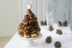 La torta de Croquembusch en la decoración de la Navidad o del Año Nuevo con una guirnalda de conos de abeto y de un ciervo figura Imagen de archivo