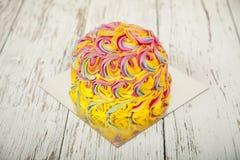 La torta de cumpleaños colorida, cubierta con la formación de hielo remolina en una tabla de madera blanca Imagen de archivo libre de regalías
