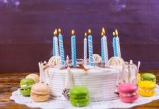 La torta de cumpleaños con las porciones de velas ardientes acerca a diverso colore Foto de archivo