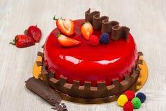 La torta de la fruta con el chocolate y la fresa en la tabla Imagenes de archivo
