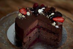La torta de la cereza del chocolate, adornada con las fresas, las galletas y la torta de frutas de la fresa Una obra maestra del  Foto de archivo
