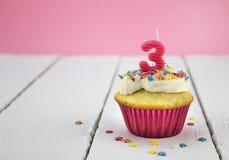 La torta de la taza del feliz cumpleaños con la estrella asperja y numera 3 Ca rosado Fotos de archivo