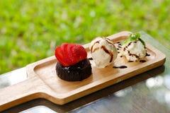 La torta de la lava del chocolate sirvió con la nata montada del helado de la fresa y de vainilla fijada en la bandeja de madera  fotografía de archivo