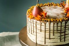 La torta de miel vierte sobre el chocolate y adornado con las peras y el espino cerval de mar en una tabla de madera Todavía del  Foto de archivo