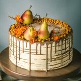 La torta de miel vierte sobre el chocolate y adornado con las peras y el espino cerval de mar en una tabla de madera Todavía del  Imágenes de archivo libres de regalías