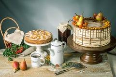 La torta de miel vierte sobre el chocolate y adornado con las peras y el espino cerval de mar en una tabla de madera Todavía del  Fotografía de archivo