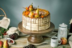 La torta de miel vierte sobre el chocolate y adornado con las peras y el espino cerval de mar en una tabla de madera Todavía del  Fotos de archivo libres de regalías