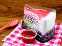 La torta del crespón del arco iris en caja plástica y la fresa dulce sauce en fondo de madera Imágenes de archivo libres de regalías