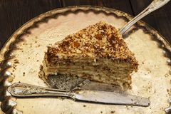 La torta del ` s de Napoleon con natillas se adorna con las pasas y el chocolate rallado en un disco de plata en una tabla de mad imagenes de archivo