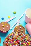 La torta di compleanno del cioccolato al latte con Candy lustrato multicolore spruzza il fondo rosa di carta del blu delle paglie immagine stock libera da diritti