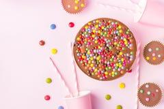 La torta di compleanno del cioccolato al latte con Candy lustrato multicolore spruzza il fondo rosa delle paglie rosa di carta de fotografia stock