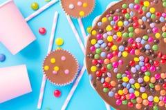 La torta di compleanno del cioccolato al latte con Candy lustrato multicolore spruzza le paglie barrate di carta rosa delle tazze fotografia stock libera da diritti