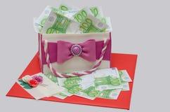 La torta di compleanno gradisce la borsa della donna con cento euro Fotografia Stock