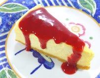 La torta di formaggio al forno con la salsa del lampone rosso è servito sul piatto bianco e blu Immagini Stock