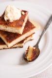 La torta di formaggio dei pezzi e una crema, versano il miele, un cucchiaio, Fotografia Stock Libera da Diritti