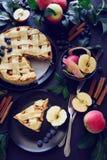 La torta di mele americana di tradizione con le mele, il mirtillo e la cannella ha decorato le foglie della mela su fondo di legn fotografia stock