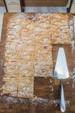 La torta di sabbia con inceppamento ed i dadi sulla tavola, intero pezzo, incide i pezzi, vista superiore Immagine Stock