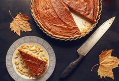 La torta di zucca con una fetta e un autunno copre di foglie thanksgiving Fotografia Stock