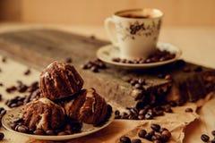 La torta dulce con una cereza y los granos de café en el fondo de la taza de café y calientan la bufanda hecha punto Fondo sabros Imágenes de archivo libres de regalías