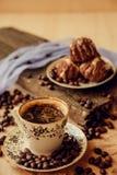 La torta dulce con una cereza y los granos de café en el fondo de la taza de café y calientan la bufanda hecha punto Fondo sabros Imagen de archivo