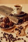 La torta dulce con una cereza y los granos de café en el fondo de la taza de café y calientan la bufanda hecha punto Fondo sabros Foto de archivo