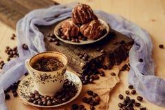 La torta dulce con una cereza y los granos de café en el fondo de la taza de café y calientan la bufanda hecha punto Fondo sabros Fotos de archivo
