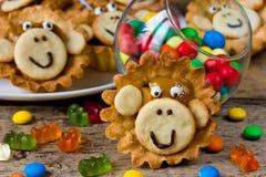 La torta festiva formó el primer de la cara del mono en el backgroun de madera Imagen de archivo libre de regalías