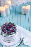 La torta hecha en casa adornó bayas en la placa sobre fondo de madera de la turquesa Foto de archivo libre de regalías