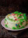 La torta hecha en casa de la amapola con la galleta de la nuez y la crema de las natillas adornó el caramelo de los dulces en fon Foto de archivo libre de regalías