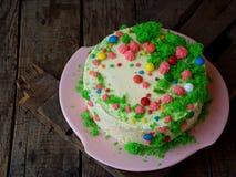 La torta hecha en casa de la amapola con la galleta de la nuez y la crema de las natillas adornó el caramelo de los dulces en fon Foto de archivo