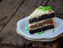 La torta hecha en casa de la amapola con la galleta de la nuez y la crema de las natillas adornó el caramelo de los dulces en fon Fotos de archivo libres de regalías