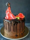 La torta hecha a mano cubrió un esmalte negro del chocolate con la figura de una muchacha en un vestido rojo y una rosa roja en u Fotografía de archivo libre de regalías