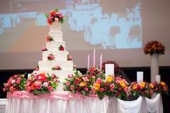 La torta hermosa adorna con la rosa, la flor y la vela del rosa para la ceremonia de boda Imagen de archivo libre de regalías