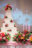 La torta hermosa adorna con la rosa, la flor y la vela del rosa para la ceremonia de boda Fotos de archivo