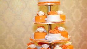La torta nunziale coperta in arancio e nel bianco ha rotolato il fondente archivi video