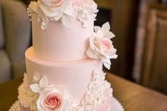 La torta nunziale rosa a file bei quattro eleganti decorata con le rose fiorisce Concetto floreale dal mastice dello zucchero fotografie stock