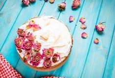 La torta poner crema blanca adornó seco subió en fondo de madera azul Foto de archivo