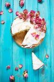 La torta poner crema blanca adornó seco subió en fondo de madera azul Imagen de archivo