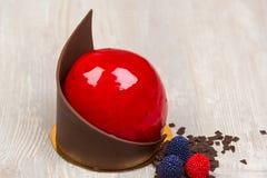 La torta roja del esmalte del chocolate en la tabla Fotos de archivo