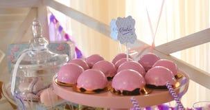 La torta rosada hace estallar en una tabla del postre en la celebración del partido o de la boda metrajes