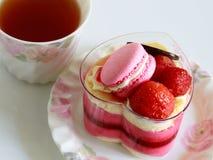 La torta rosada hermosa del yogur adorna con el macaron y fresa y taza de té Fotos de archivo