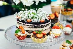 La torta se adorna con crema de las flores blancas y del requesón de las fresas Arreglado alrededor de las magdalenas foto de archivo libre de regalías
